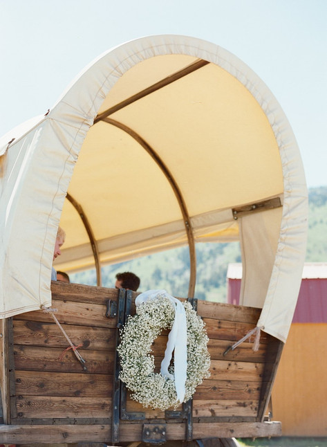 Old Fashioned Wooden Wagon with a Round White Canvas Cover and a Wreath of Baby's Breath on the Back