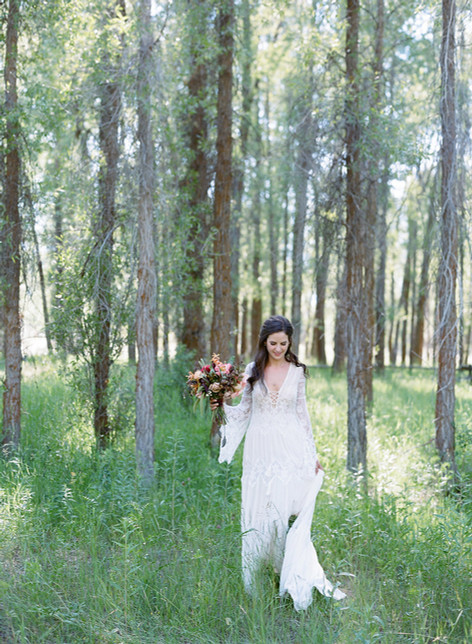 Bride Walking Through the Woods with Bouquet