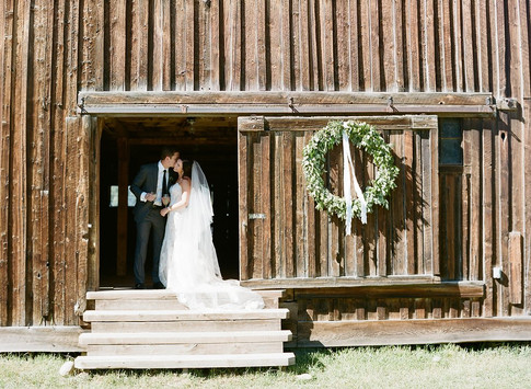 Bride and Groom Kissing in a Barn Doorway with a Green Wreath Hanging Next to Them