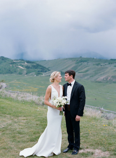 Bride and Groom Looking at Eachother on a Mountainside