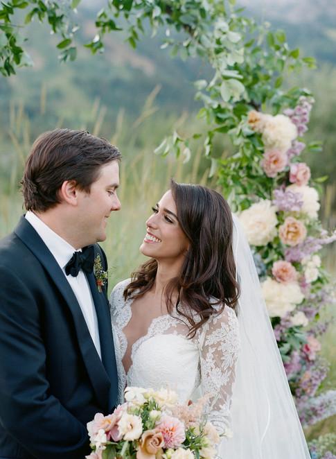 Bride Smiling at Groom in Flower Arch.jpg