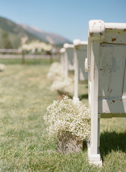 White Wedding Benches with Small Arrangements of Baby's Breath in the Aisle