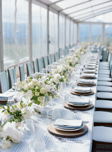Long Wedding Reception Table with White and Green Flowers, Light Blue and Wood Accents