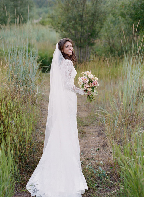 Bride Standing in Tall Grass with a Light Pink Bridal Bouquet