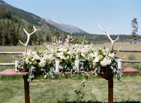 Wood Wedding Altar Table with Large White and Green Flower Arrangment and Large Antlers on Both Sides
