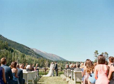 Bride and Groom Facing Eachother During Wedding Ceremony with Mountains in the Background