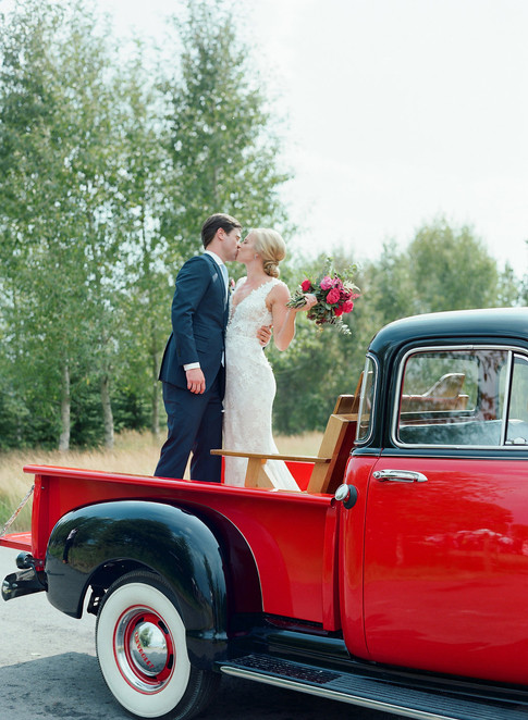 Bride and Groom Standing and Kissing in the Bed of an Old Fashioned Ford Truck