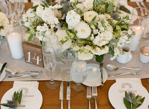 Tablesetting with a Blue Thisle on a White Menu in front of a White and Green Floral Centerpeice