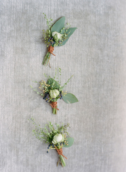 Three Green and White Boutonnieres on Grey Velvet