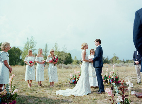 Bride and Groom Facing each other with Three Bridesmaids Watching