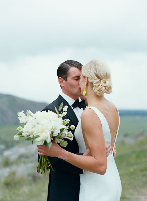 Bride Holding a Wedding Bouquet and and Kissing the Groom