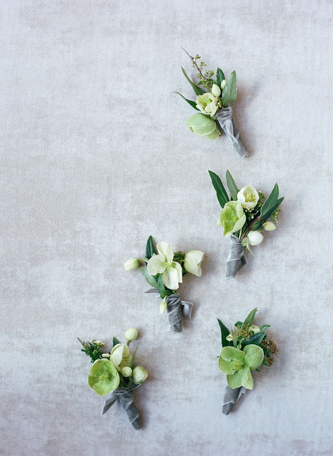 Five White and Green Boutonnieres on a Grey Background