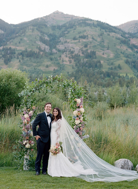 Bride and Groom Smiling in front of Flower Arch in Mountains