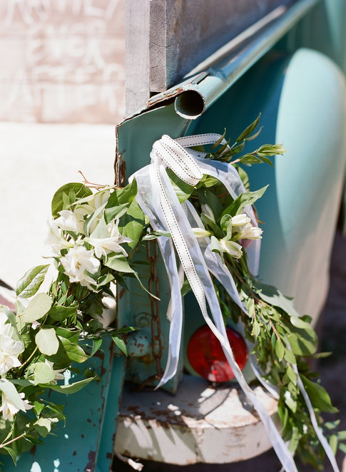 Old Fashioned Blue Ford Truck with Green Garland tied to the back with White Ribbon