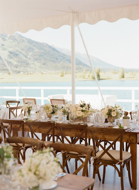 Long Wooden Table in a White Tent Overlooking a Lake