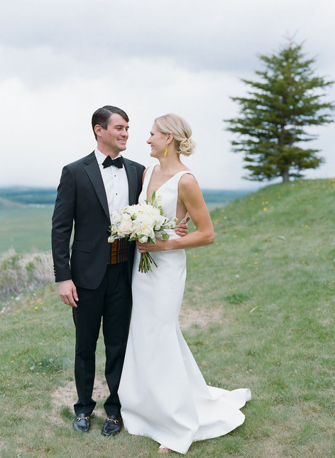 Bride and Groom Smiling at Each other on a Mountainside