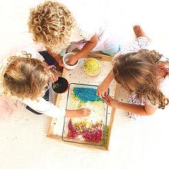 niñas jugando con arroz de colores, motricidad fina