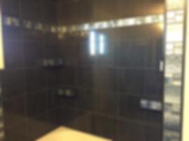 Black porcelain tile w/ glass mosaic accents