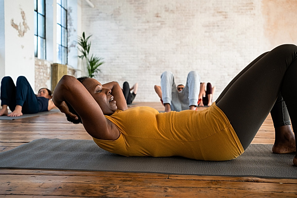 """Brenda Nassali-Liston Black Pilates Teacher demonstrates the Curl Up exercise to clients"""