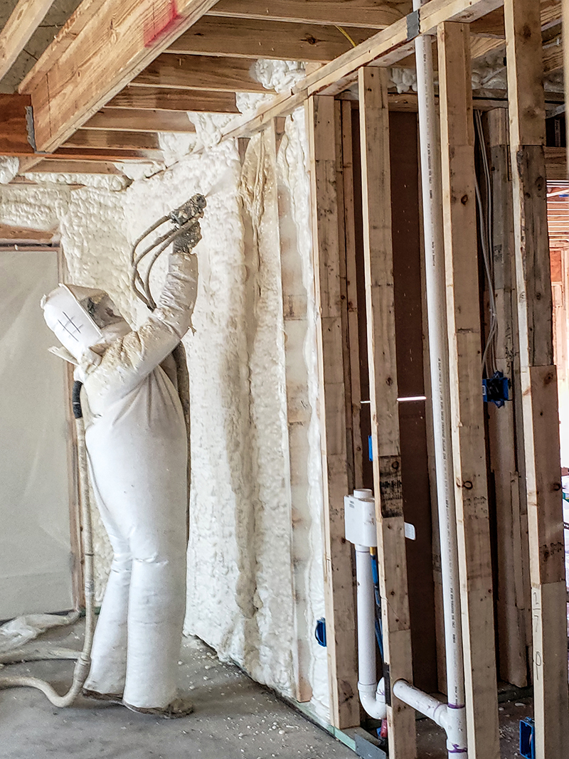 Spaying foam insulation into the cavities of the wall