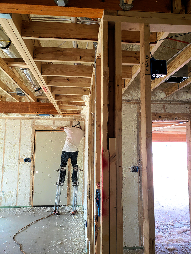 Scraping off the excess foam insulation
