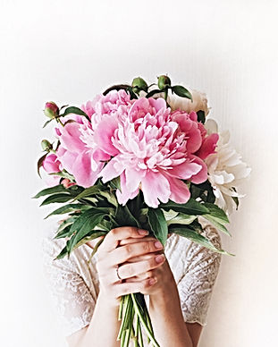 Girl with pink peonies bouquet at white