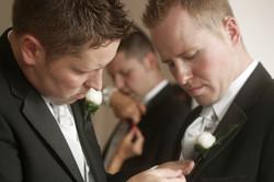 Noosa wedding groom pinning flowers