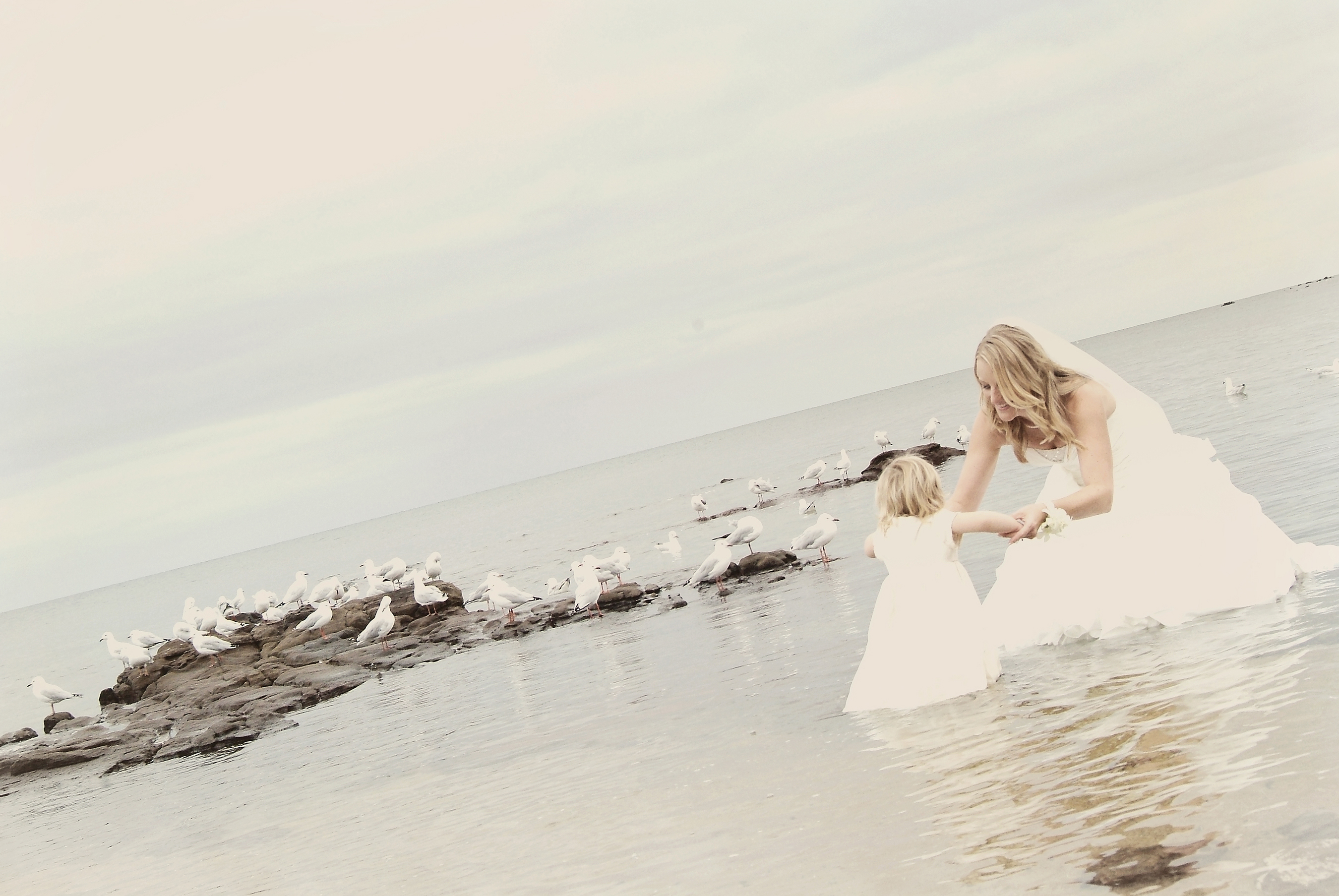 bride and flower girl wade in beach