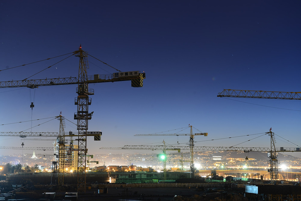 Construction site with cranes at night.