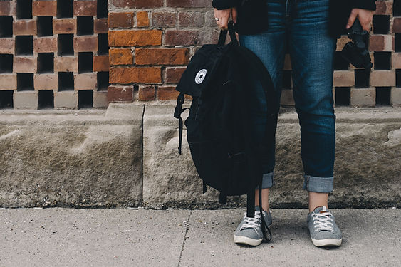 A student holding their rucksack whilst waiting on the pavement outside their student accommodation