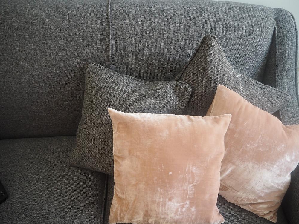Pink velvet cushion on grey sofa