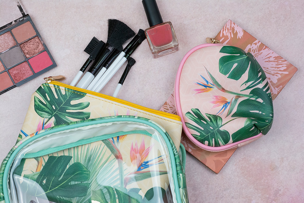 Set of three tropical patterned vanity bags with cosmetics scattered around them.