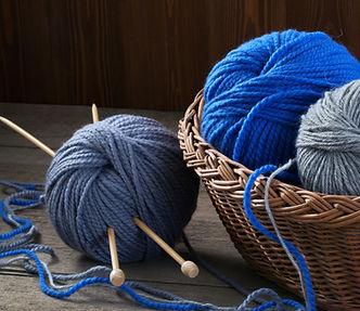 basket of yarn and knitting needles