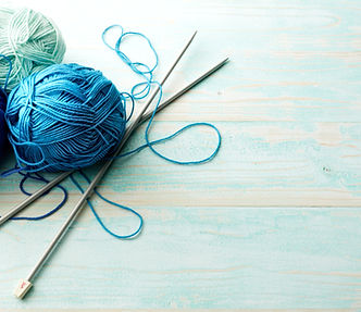 blue and green yarn balls with knitting needles