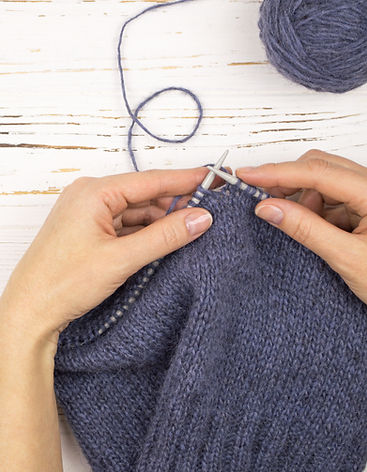 pair of hands holding a garment that is being knitted