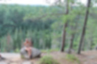 Girl is sitting on the rock on he edge of the cliff on Two Rivers Trail in Algonquin