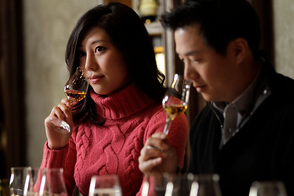 asian couple at the wine tasting. They are smelling the wine