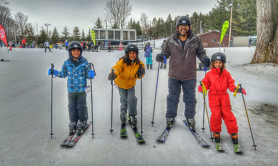 Family, dad with his kids, are skiing at Snow Valley