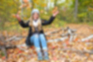 Girl enjoying fall colours buy throwing leaves to the air