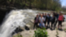 group of people standing by the waterfall