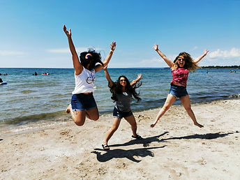Girls jumping on the sandy beach