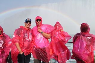 two guys are taking Hornblower boat tour in niagara falls. They have rain jackets on them