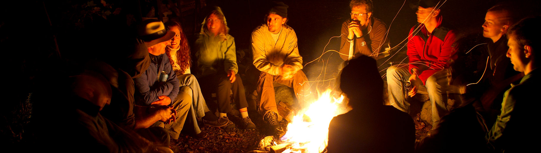 group of people sitting along campfire