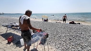 Chef cooking filipino bbq on the beach