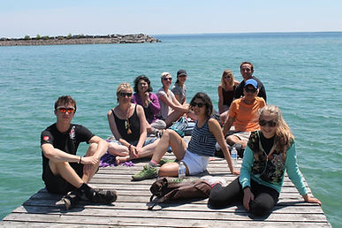 Group of people sitting one the dock