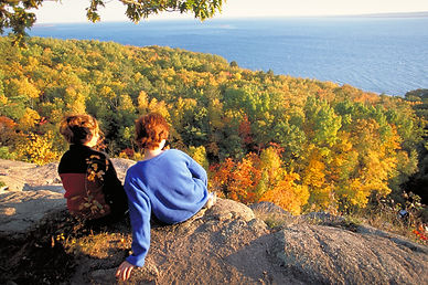 two people looking from the lookout on the lake. Lake surrounded by fall colours