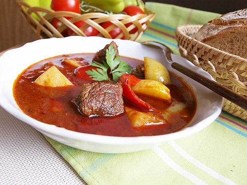 Hungarian goulash on the plate with basket of vegetable and basket of bread