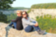 Two people sitting on the edge of the cliff at the state park