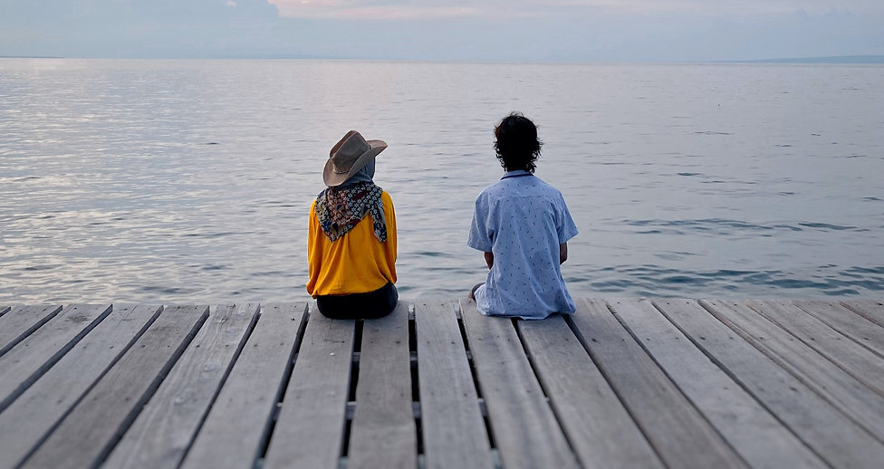 a couple sitting apart on a pier and gazing over out to sea