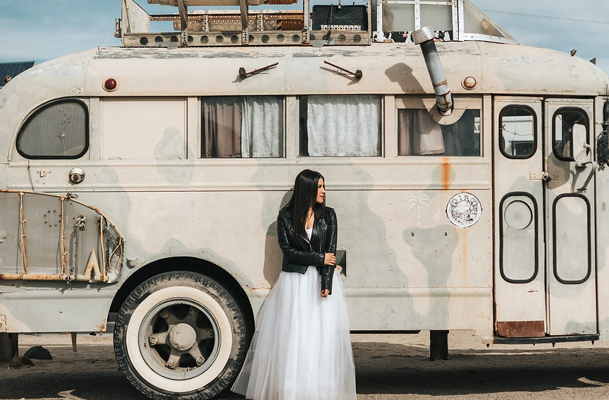 a woman in a wedding dress and leather biker jacket standing by a vintage camper van